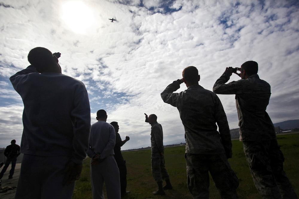 New members of the California Air National Guard watch a plane carrying seasoned pararescuemen fly above during traning held at Moffett Federal Airfield.