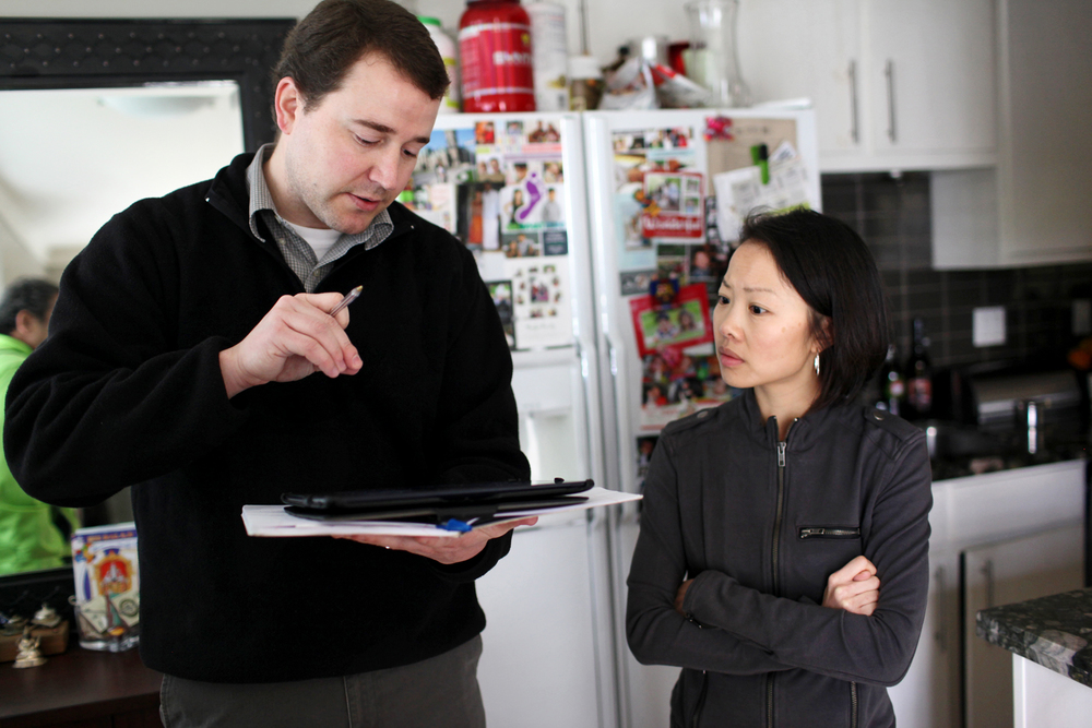 Todd Rogers explains to Evandale Avenue resident Helen Tsao the levels of TCE found in her unit, Mar. 25, 2013. Tsao said she agreed to the testing because she is concerned about health and the future idea of having a child. TCE can affect the cardiovascular development in a fetus and other defects.
