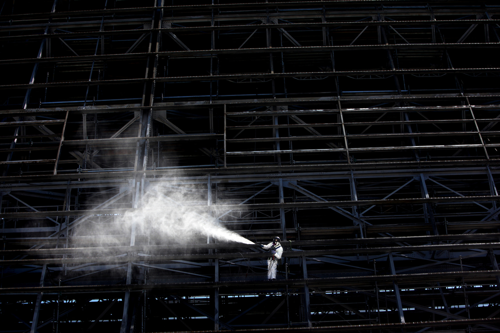A worker uses a high pressure hose for a final wash of Hangar One, July 19, 2012. The walls of Hanger One were lined with abestos. TCE was also found seeping there.
