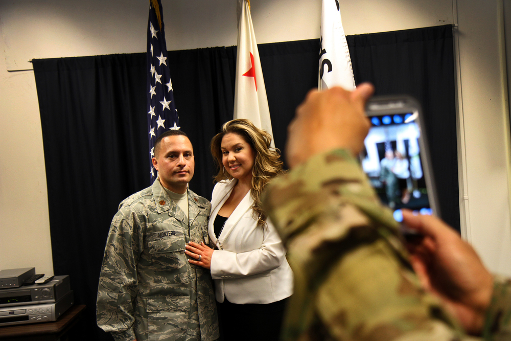 Air National Guard Major Montero has his photo taken with his wife after his promotion ceremony, at Moffett Federal Airfield.