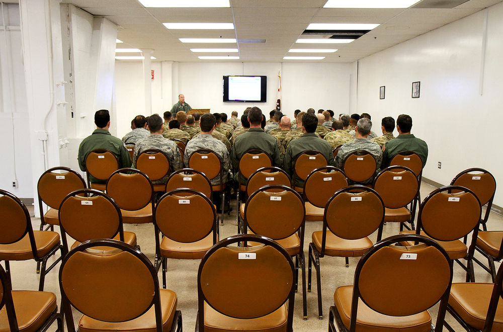 Airmen listen to instruction for deployment to Afghanistan, during the Personnel Deployment Function line, Mar. 2, 2013.