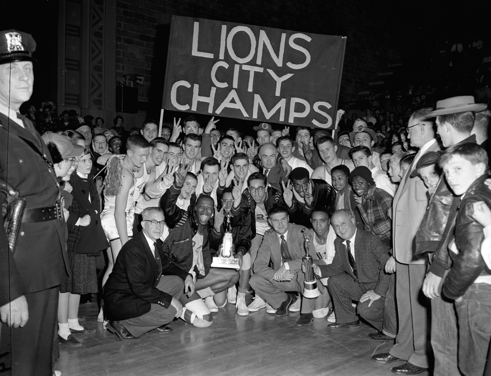 The Lanphier Lions and their fans gathered around the trophies they earned for winning the 1955 city high school basketball championship at the Illinois State Armory on Jan. 22. The jubilant moment began a stretch of four consecutive wins for the Lions and coach Arlyn Lober, who ranks second all-time with nine City Tournament championships. Lober's team also shared the title in 1954, his first year as Lions coach; this was their first outright win. One of the players on the team that year was Bob Nika, who succeeded Lober as Lanphier coach in 1974 and won six City Tournament titles himself. The Lions, by the way, lead the title count with 19 outright wins, followed by Springfield High, Southeast and Sacred Heart-Griffin and its predecessors, Cathedral and Griffin. The four city high schools will square off again this weekend for another title at the Prairie Capital Convention Center, the event's 65th year. Published Jan. 18, 2014. File/ The State Journal-Register