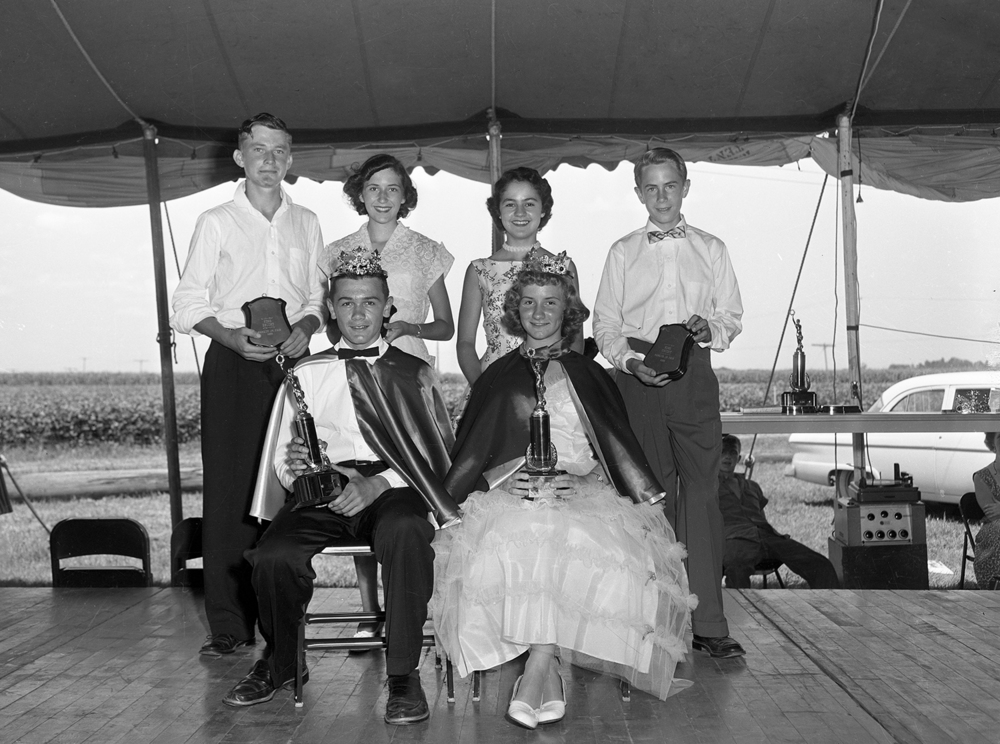 In addition to the dairy, poultry, swine and rabbits being judged at the 1955 Sangamon County Fair in New Berlin, young men and women were also being scrutinized for their talents and appearance. Unlike the farm animals, they chose to participate in the Junior Journal and Register king and queen contest. WTAX radio's Bill Miller was Master of Ceremonies for the talent competition and coronation, which revealed Frank Wables and his cousin Judy Richardson as the new royal couple. Escorts, standing from left, were Walter Whitaker, Phyllis Jennings, Barbara Nudo and Tom Delker. The 2014 Sangamon County Fair begins Wednesday, June 18. Published June 7, 2014. File/ The State Journal-Register