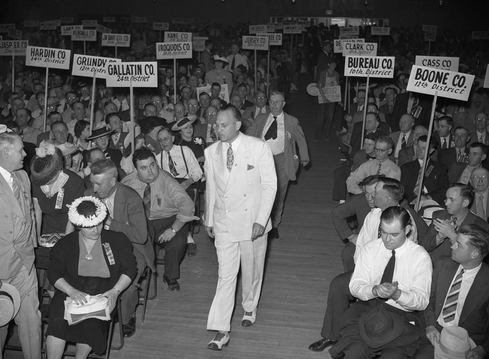 "U.S. Sen. Scott Lucas of Havana walks toward the front of a crowd of delegates on the floor of the Illinois State Armory during the state Democratic convention on June 22, 1940. After a divisive spring that saw intraparty fighting in the primary over the races for governor, U.S. senator and state auditor, the Democrats had found harmony in time for their meeting in Springfield. In his keynote speech, Lucas outlined the party's unequivocal support for a third term for President Franklin Roosevelt and expressed support for his administration's policies. But it wasn't Lucas' speech from the convention that made news. Chicago Mayor Edward Kelly endorsed Lucas as a vice presidential candidate to run with Roosevelt, and it was accepted by the delegates with a ""hearty salvo of 'ayes,' "" according to The Illinois State Journal. Lucas, Kelly said, ""has demonstrated his qualities as statesman, is unquestionably patriotic, has won the confidence of farmers, labor and industry and is a staunch supporter of the Roosevelt policies."" Lucas was not chosen by Roosevelt, however, but continued to serve in the Senate until 1951, including as Senate majority leader from 1948 to 1950. File/ TheState Journal-Register"