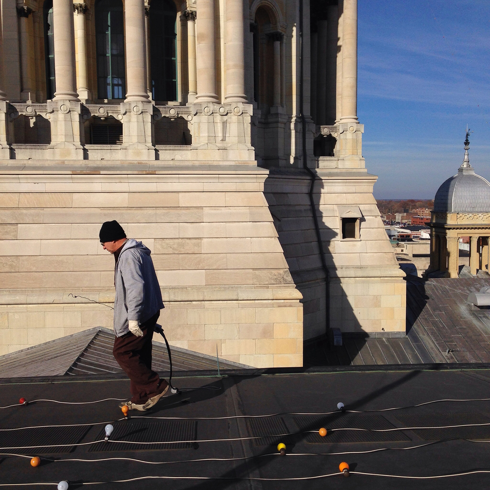 Installing holiday lights on the roof of the State Capitol