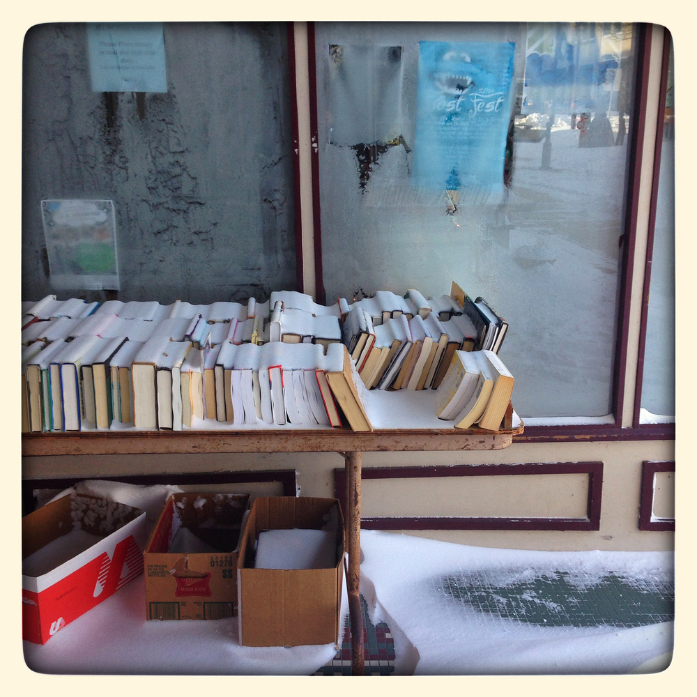 Books on a table outside Prairie Archives collected snow during a winter storm.