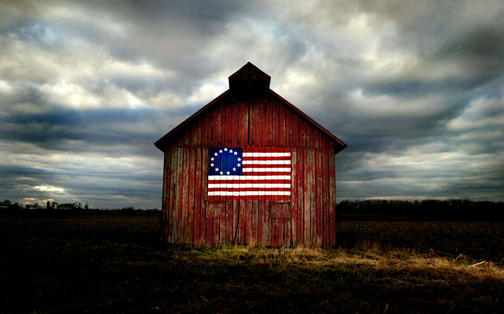 "The Wiese family barn stands braving storm clouds with a with a historic Besty Ross American Flag painted in rememberance of the September 11 attacks just north of Carlinville on Route 4. ""My son helped paint it to remember that day,"" Gloria Wiese said. ""You wouldn't believe how many people stop and ask us about it."" The Wiese family settlement dates back to 1853 in Macoupin County and the farm has been passed down through generations ever since.