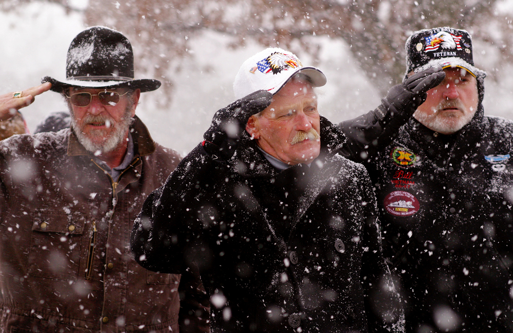 From left, Charlie Brightman of Greenup, Bob Mathias of Charleston, and Bill Martin of North Pekin salute as the American flag passes after a Christmas remembrance ceremony at the Illinois Vietnam Veterans Memorial at Oak Ridge Cemetery in Springfield Saturday afternoon. Friends and family members of the 82 soldiers still listed as prisoners of war or missing in action placed ornaments on a blue spruce near the memorial, and the Land of Lincoln Barber Shop Chorus sang Christmas songs. Kristen Schmid Schurter