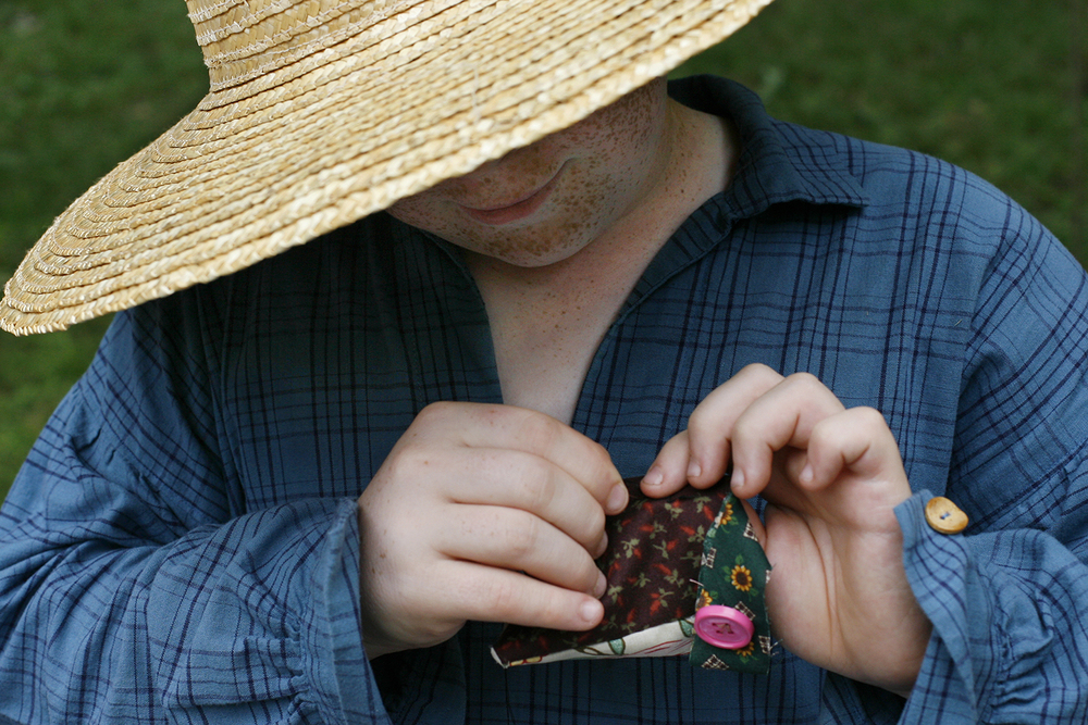 Mason Rickard of Mason City sews a button on a coin pocket during the Summer Festival at Lincoln's New Salem State Historic Site Saturday, June 11, 2011. Ted Schurter/The State Journal-Register