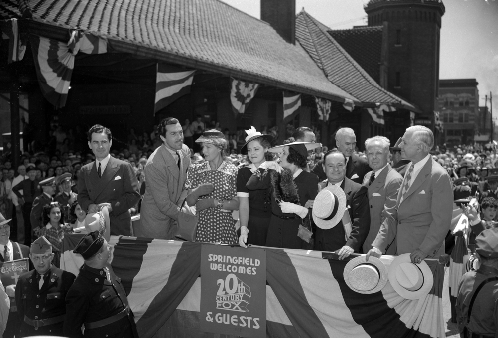 The visiting celebrities were welcomed to Springfield after their special train arrived at the Alton (now Amtrak) Station. From left, Lowell Thomas, Cesar Romero, Binnie Barnes, Arleen Whelan, Alice Brady, Eddie Collins, Springfield Mayor John W. Kapp, and George M. Maypole, president pro tem of the Illinois Senate.  Below , Mary Lou Wangard of 624 N. Second St. got a glimpse of screen luminaries at the premiere show Tuesday night with the help of Christy Wilbert, Twentieth Century Fox studio official, who hoisted her to his shoulders when he saw her standing on her tiptoe in the throng which surrounded the theater. Her mother, Mrs. J.W. Wangard, is standing in the background.  File/The State Journal-Register