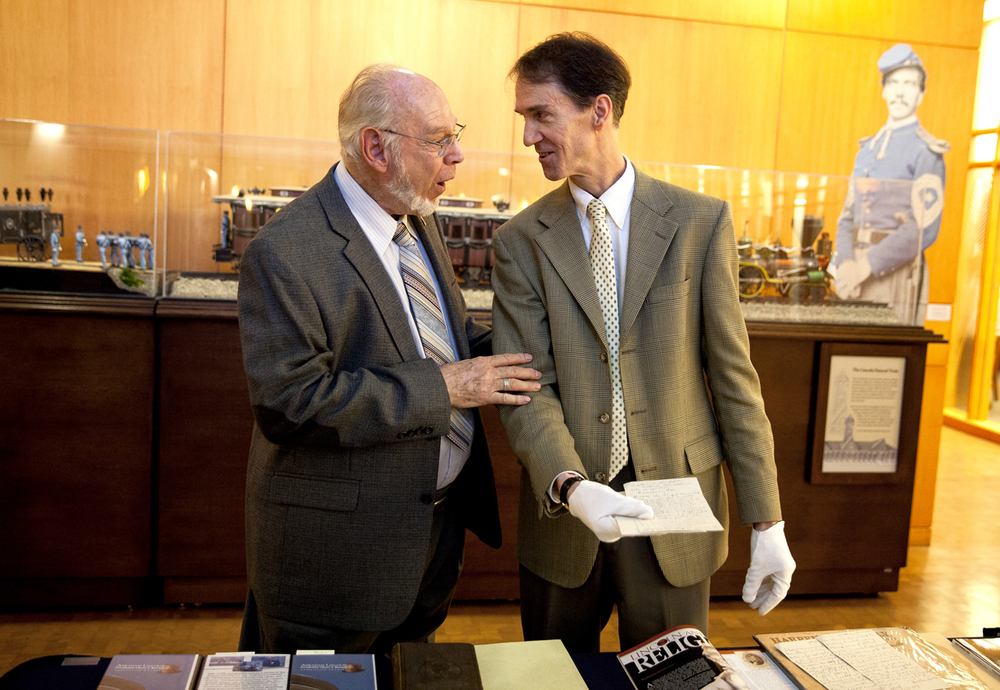 Ronald Rietveld, left, who discovered as a boy in 1952 the only known photograph of Abraham Lincoln lying in his coffin, presented James Cornelius, curator of the presidential library's Lincoln Collection with his notes related to the discovery during a press conference at the presidential library Tuesday, Oct. 7, 2014. Rietveld went on to become a history prefessor at California State University, Fullerton. The two laughed when Cornelius told him the library's preservationist would clean the papers. Rich Saal/The State Journal-Register