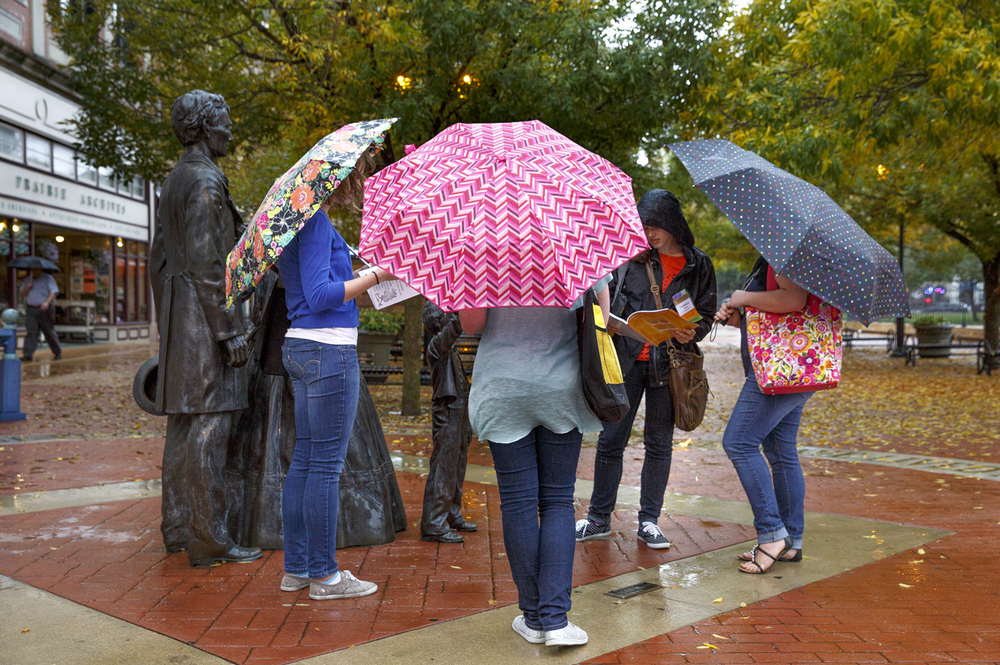 A group of students from Olivet Nazarene University pause at the Lincoln family sculpture on the Old Capitol Plaza Thursday, Oct. 2, 2014, during a rain shower. The women are attending a conference at a downtown hotel and were out on their lunch break. Rich Saal/The State Journal-Register