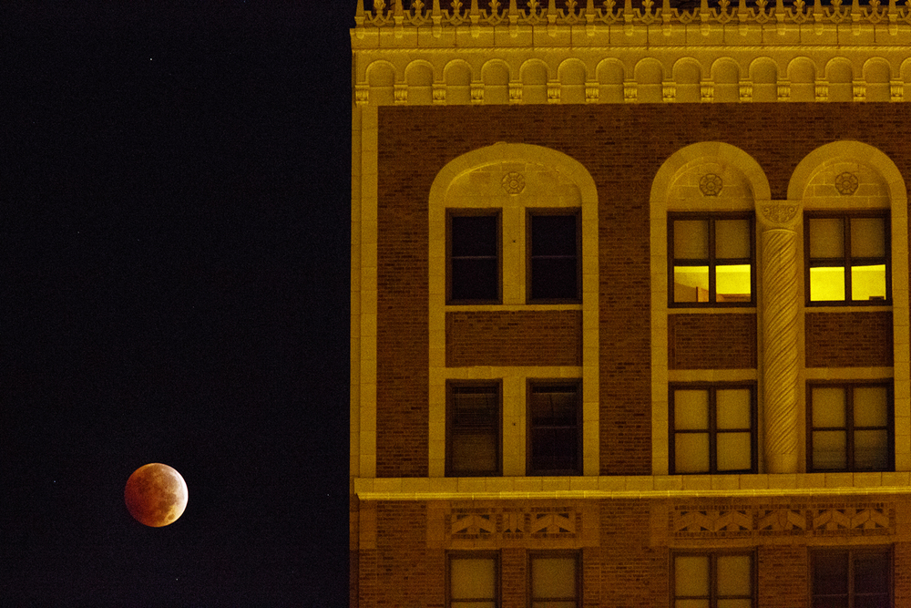 "A total lunar eclipse, the second this year, appears to hover near the Myers Brothers building an hour before sunrise Wednesday, Oct. 8, 2014. It takes on a coppery-red color as it slips into the earth's shadow, which leads some to call it a ""blood moon."" Rich Saal/The State Journal-Register"