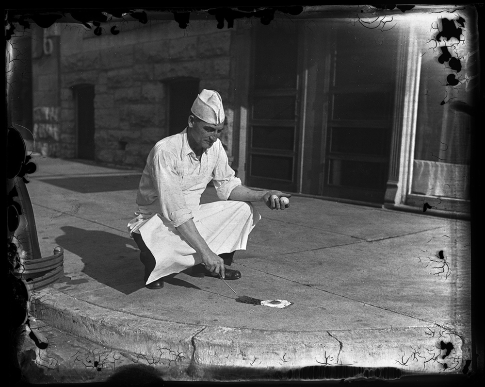 "T.M. Travis of Travis Cafeteria at 624 E. Capitol, attempting to fry an egg on sidewalk July 20, 1930. ""Heat in City Reaches 100,"" story and photo published July 20, 1930, File/The State Journal-Register"