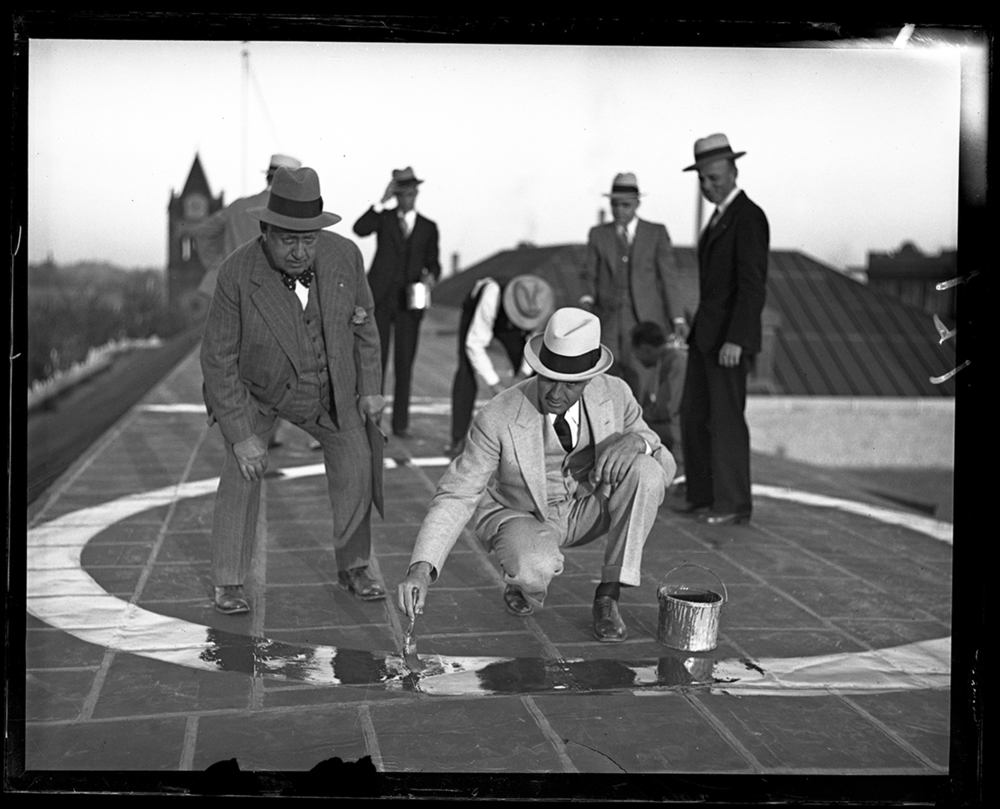 Postmaster William Conkling, left, and Newman Stirewalt, president of the American Business Club, painting air traffic directional sign on the Federal Building roof, Oct. 2, 1930. File/The State Journal-Register