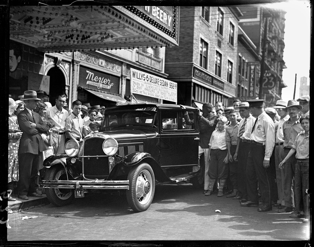 A sign atop this 1930 model Willys 6 Deluxe Sedan says it is so easy to handle in heavy traffic, it can be driven blindfolded. Parked under the Orpheum Theater marquee, a crowd gathers to see a blindfolded Billy Russell, seen next to the driver's door, give it a try, date unknown. File/The State Journal-Register