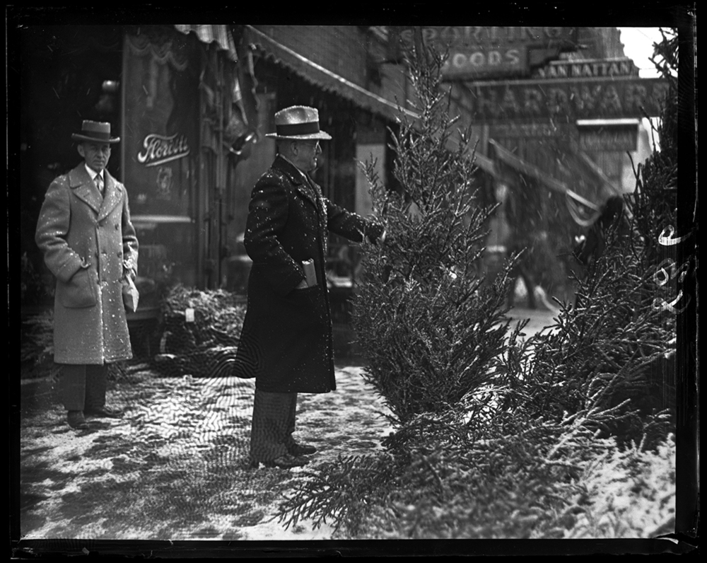 Carl D. Franke chooses a Christmas tree from the sidewalk in front of Van Nattan Hardware on Monroe Street, Dec. 18, 1930. File/The State Journal-Register