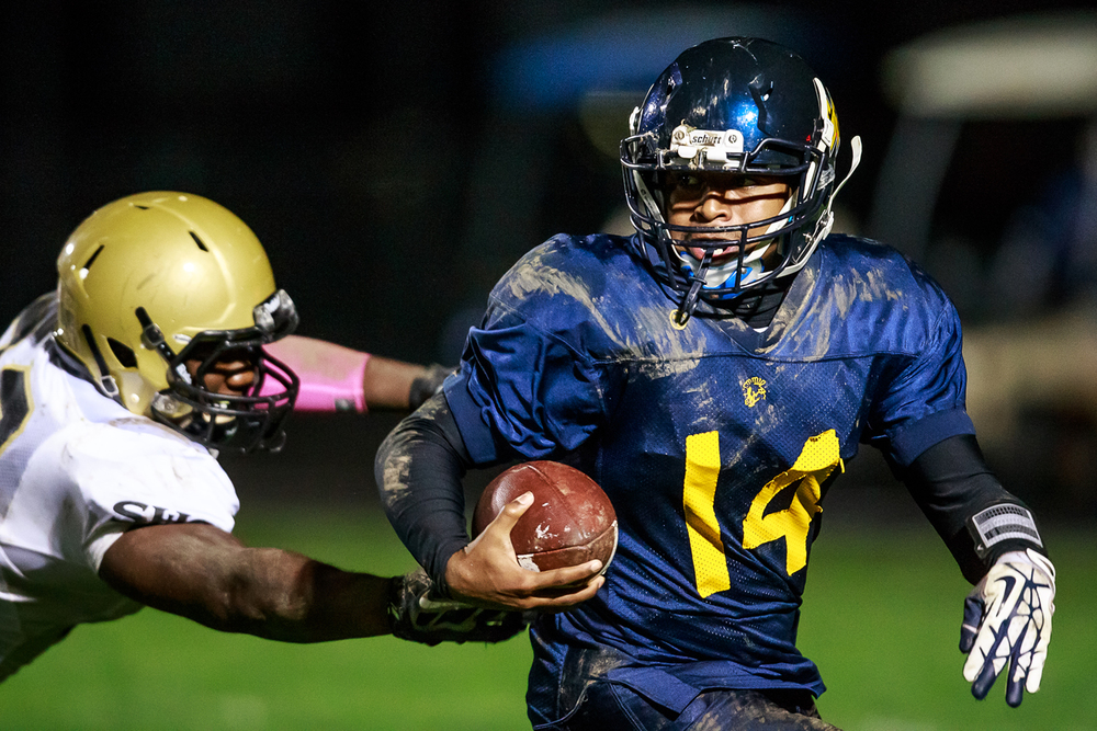 Southeast quarterback Isaiah Timms (14) escapes a sack from Sacred Heart-Griffin's DJ Mackey (38) during the second half at Southeast High School, Friday, Oct. 17, 2014, in Springfield, Ill. Justin L. Fowler/The State Journal-Register