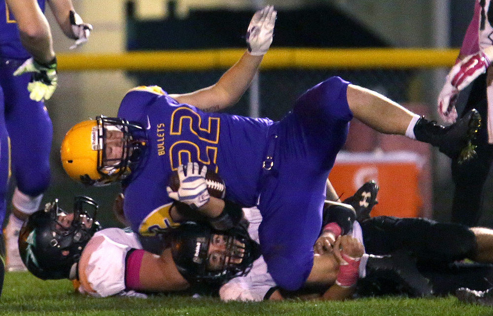 Bullets ballcarrier Tate Manka scores his team's second touchdown of the night. Defending on bottom of heap are Athens players Kyle Thomas at right and Jacob Taylor. The Williamsville Bullets defeated the Athens Warriors 34-13 in high school football action at Paul Jenkins Field in Williamsville on Friday, Oct. 17, 2014. David Spencer/The State Journal-Register