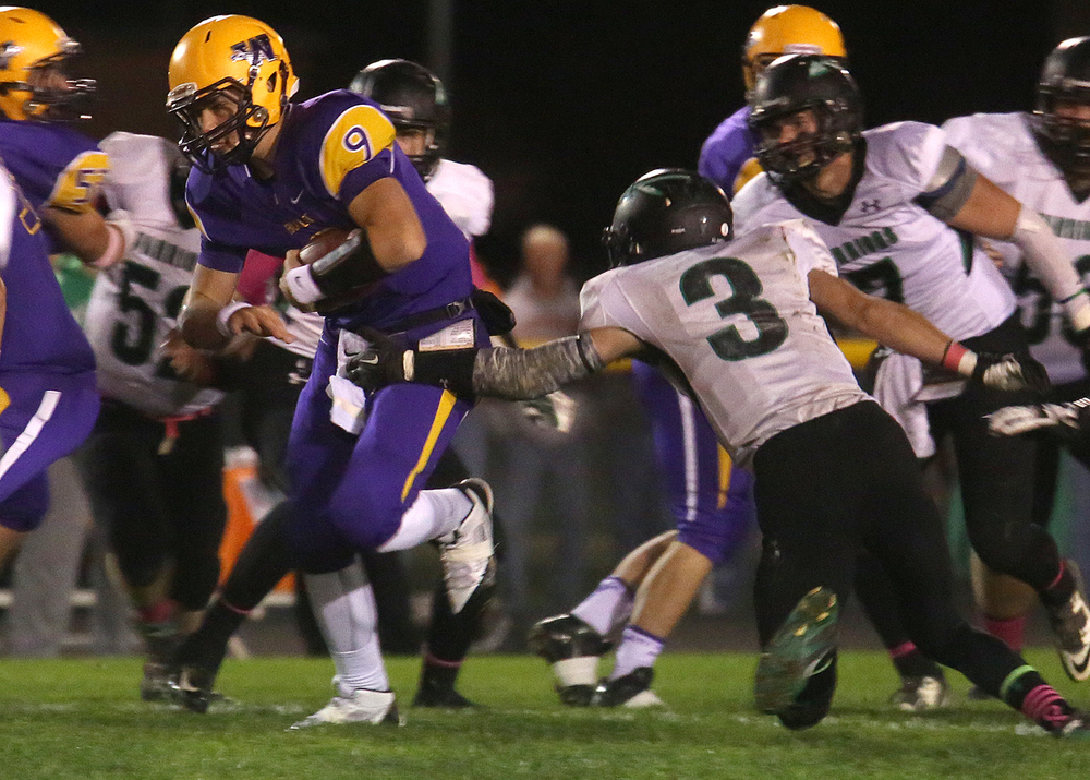 Bullets quarterback Luke Bleyer scoots for yardage. At right defending is Warriors player Hunter Hammitt. The Williamsville Bullets defeated the Athens Warriors 34-13 in high school football action at Paul Jenkins Field in Williamsville on Friday, Oct. 17, 2014. David Spencer/The State Journal-Register