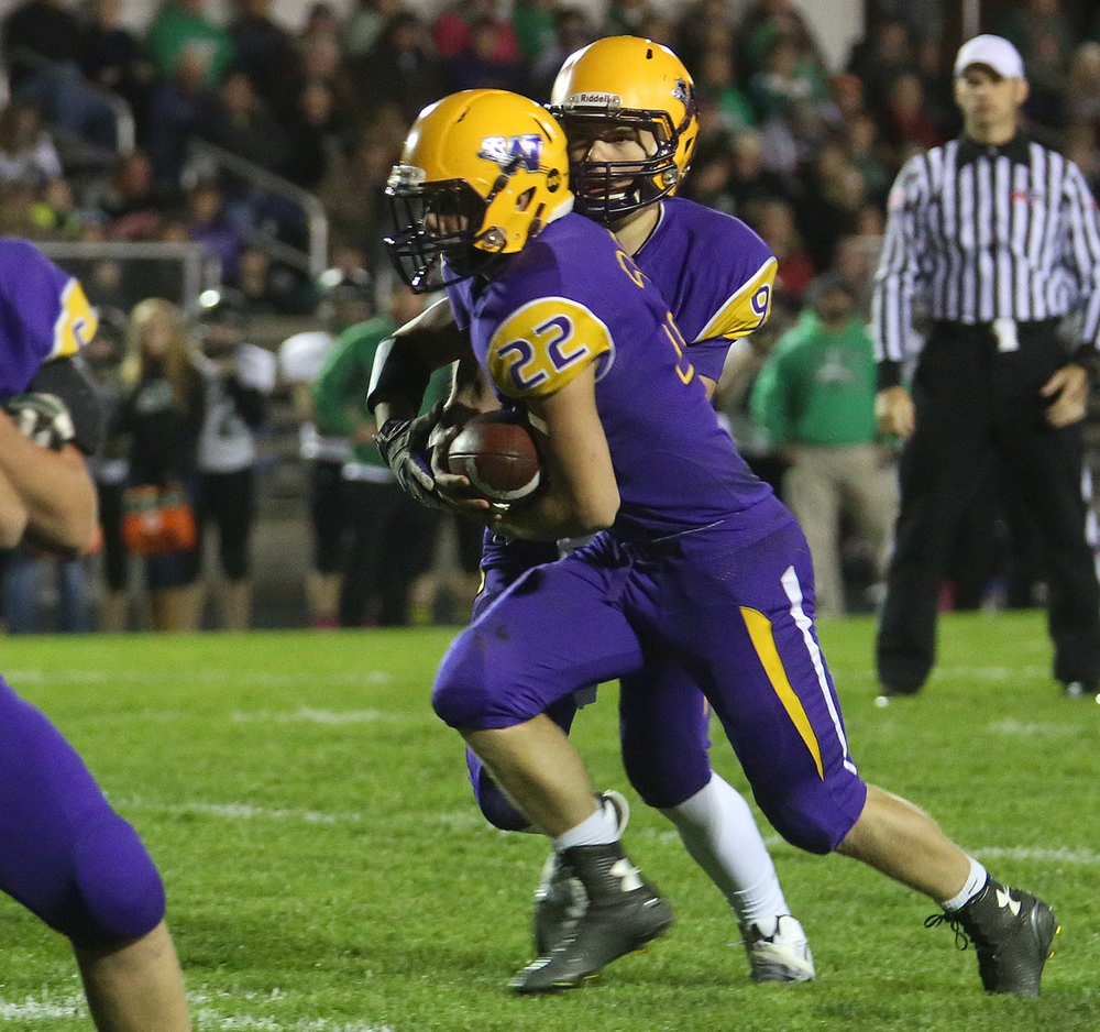 Bullets ballcarrier Tate Manka takes the handoff from quarterback Luke Bleyer and prepares to run for his team's first touchdown of the night. The Williamsville Bullets defeated the Athens Warriors 34-13 in high school football action at Paul Jenkins Field in Williamsville on Friday, Oct. 17, 2014. David Spencer/The State Journal-Register