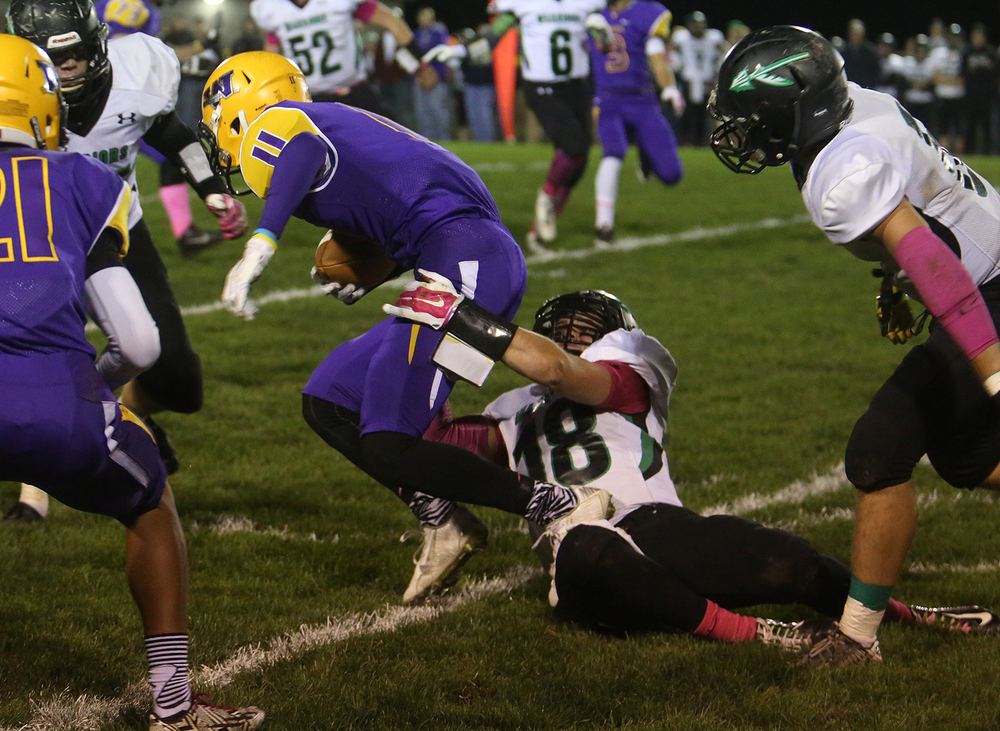 Bullets ballcarrier D'ante Cox runs while being dragged by Warrior defender Dalton Fletcher. The Williamsville Bullets defeated the Athens Warriors 34-13 in high school football action at Paul Jenkins Field in Williamsville on Friday, Oct. 17, 2014. David Spencer/The State Journal-Register