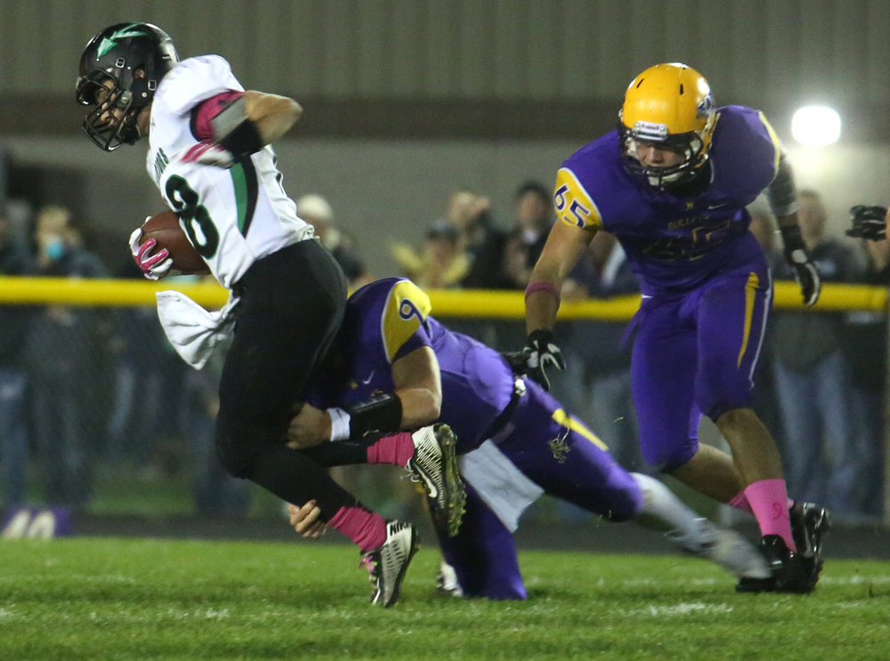 Warriors ballcarrier Dalton Fletcher is brought down by a Bullets defender. The Williamsville Bullets defeated the Athens Warriors 34-13 in high school football action at Paul Jenkins Field in Williamsville on Friday, Oct. 17, 2014. David Spencer/The State Journal-Register