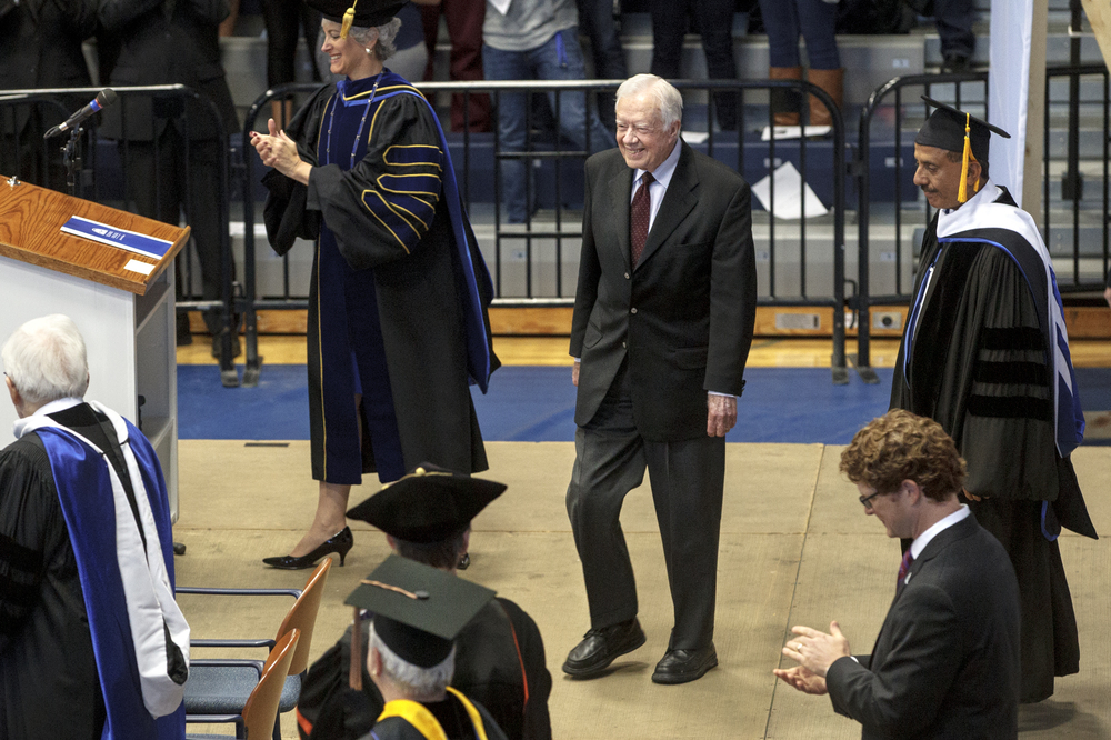 "Former President Jimmy Carter smiles as he walks onto the stage at Illinois College Tuesday, Oct. 14, 2014. Carter was at the school to help launch the ""Pathways to Peace"" initiative created by Khalaf Ahmad Al Habtoor, at left, a businessman from United Arab Emirates and supporter of the college. Ted Schurter/The State Journal-Register"