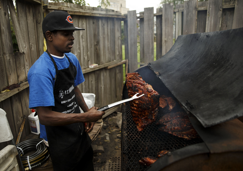 Andre Booker prepares food at P.T.'s Bar-B-Que at 601 Ninth Street Thursday, Oct. 15, 2014. The business plans to move their operation from the trailer into the former service station.  Ted Schurter/The State Journal-Register