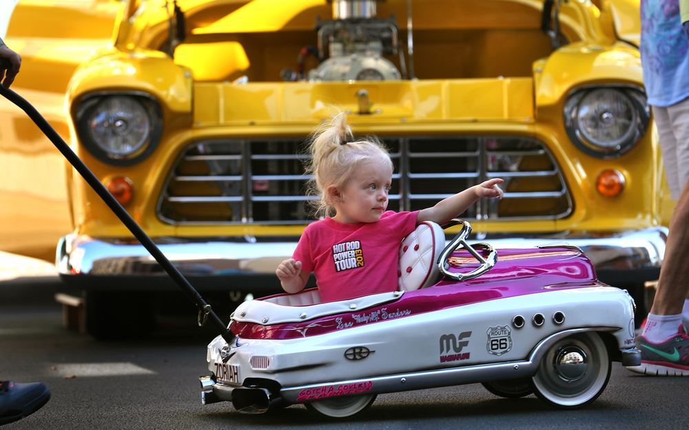 A customized 1950's pedal car was the perfect transportation for Zoe Sanders of Springfield, who along with her dad Shane Sanders pushing her, mom Nicole Sanders and grandmother Linda Wilson, were checking out the big cars on display on Sunday. Behind Zoe is a 1955 customized Chevrolet 3100 pickup truck. Zoe's dad is a member of the Peoria chapter of the Nokturnal Car Club and customized the car for his daughter. The final day of the 13th Annual International Route 66 Mother Road Festival & Car Show took place in downtown Springfield on Sunday, Sept. 28, 2014. David Spencer/The State Journal-Register