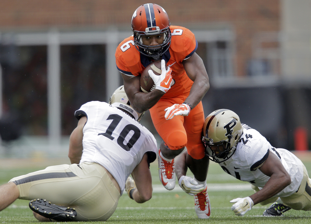 Illinois' Josh Ferguson squeezes between two Purdue defenders at Memorial Stadium in Champaign Saturday, Oct. 4, 2014. Ted Schurter/The State Journal-Register