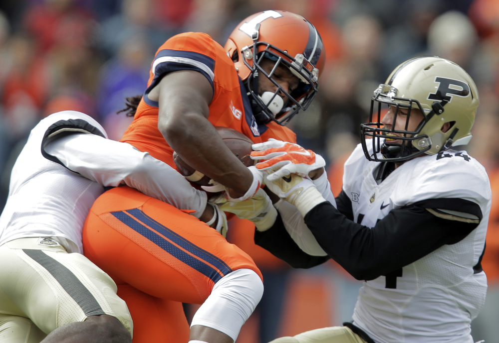 Illinois' Martize Barr is brought down by a pair of Purdue defenderrs at Memorial Stadium in Champaign Saturday, Oct. 4, 2014. Ted Schurter/The State Journal-Register