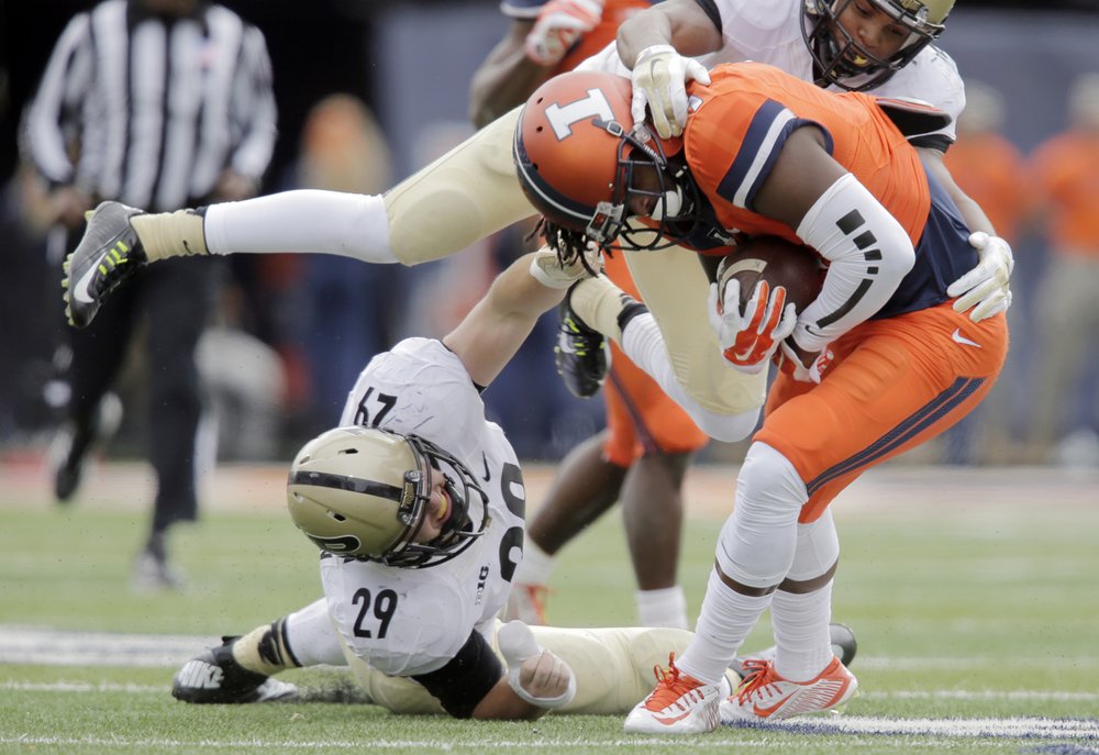 Illinois' Martize Barr struggles to stay up under pressure from Purdue defenders at Memorial Stadium in Champaign Saturday, Oct. 4, 2014. Ted Schurter/The State Journal-Register