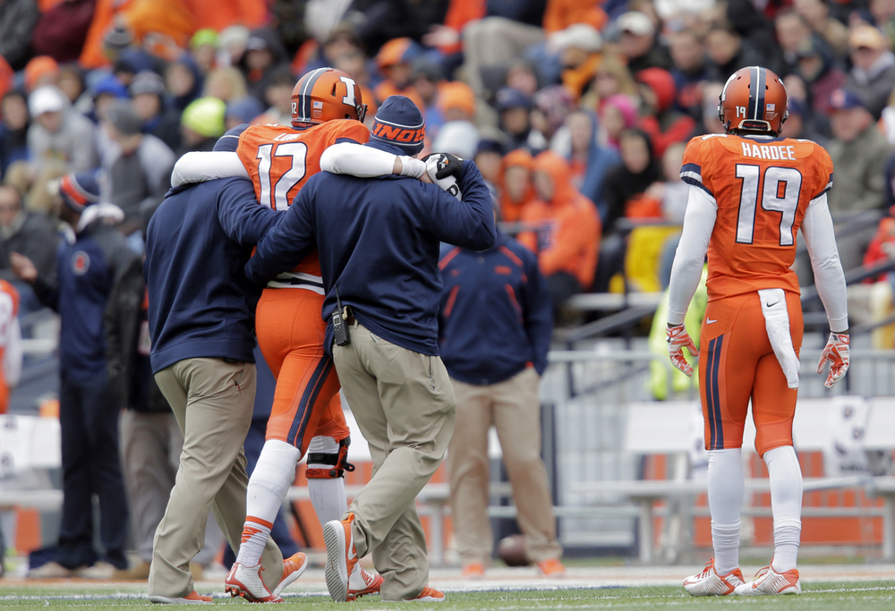Illinois quarterback Wes Lunt is helped off the field at Memorial Stadium in Champaign Saturday, Oct. 4, 2014. Ted Schurter/The State Journal-Register