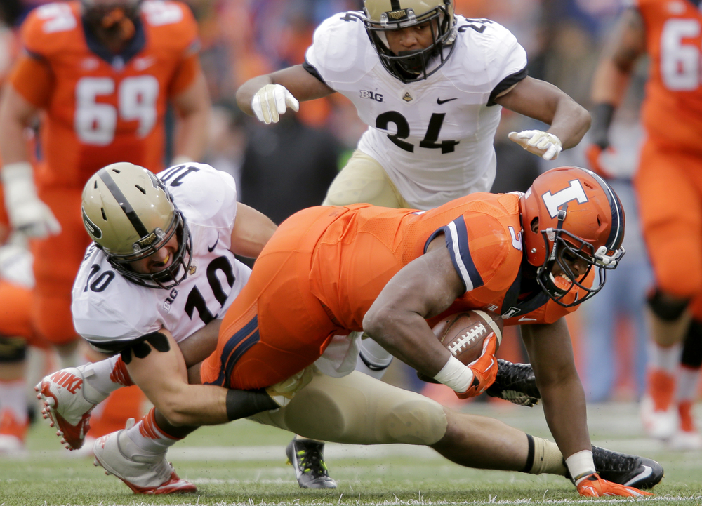 Illinois' Donovonn Young is brought down by Purdue's Sean Robinson at Memorial Stadium in Champaign Saturday, Oct. 4, 2014. Ted Schurter/The State Journal-Register