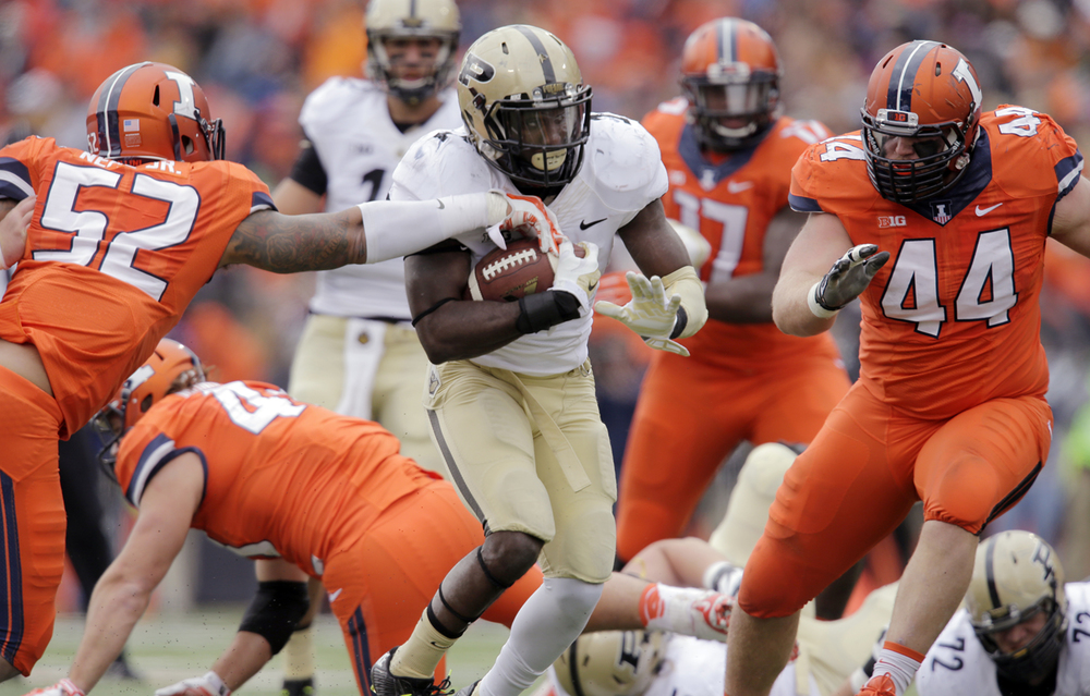 Illinois' TJ Neal Jr. gets a hand on the balll as Purdue's Akeem Hunt moves upfield at Memorial Stadium in Champaign Saturday, Oct. 4, 2014. Ted Schurter/The State Journal-Register