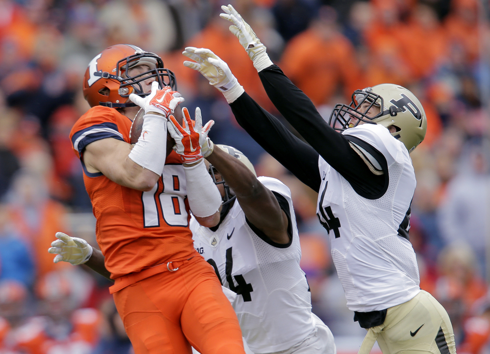 Illinois' Mike Dudek hauls in a pass under pressure from  Purdue's Frankie Williams and Landon Feichter at Memorial Stadium in Champaign Saturday, Oct. 4, 2014. Ted Schurter/The State Journal-Register