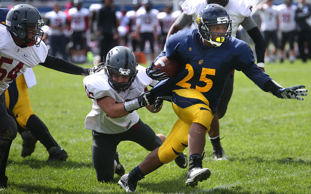 Spartans ball carrier LaPriest Green tries to keep going while Senators defender Cody Walker hangs on. The Springfield Southeast High School Spartans defeated the Springfield High School Senators 38-7 in football actions at the Spartans home field on Saturday, Oct. 4, 2014. David Spencer/The State Journal-Register