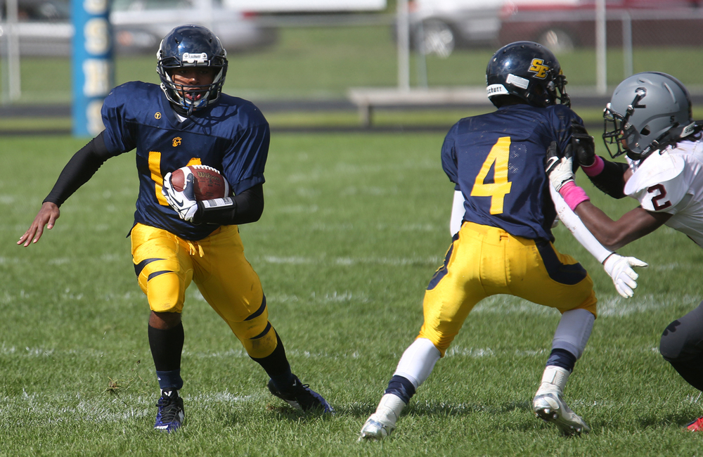Spartans quarterback Isaiah Timms runs for yardage. The Springfield Southeast High School Spartans defeated the Springfield High School Senators 38-7 in football actions at the Spartans home field on Saturday, Oct. 4, 2014. David Spencer/The State Journal-Register