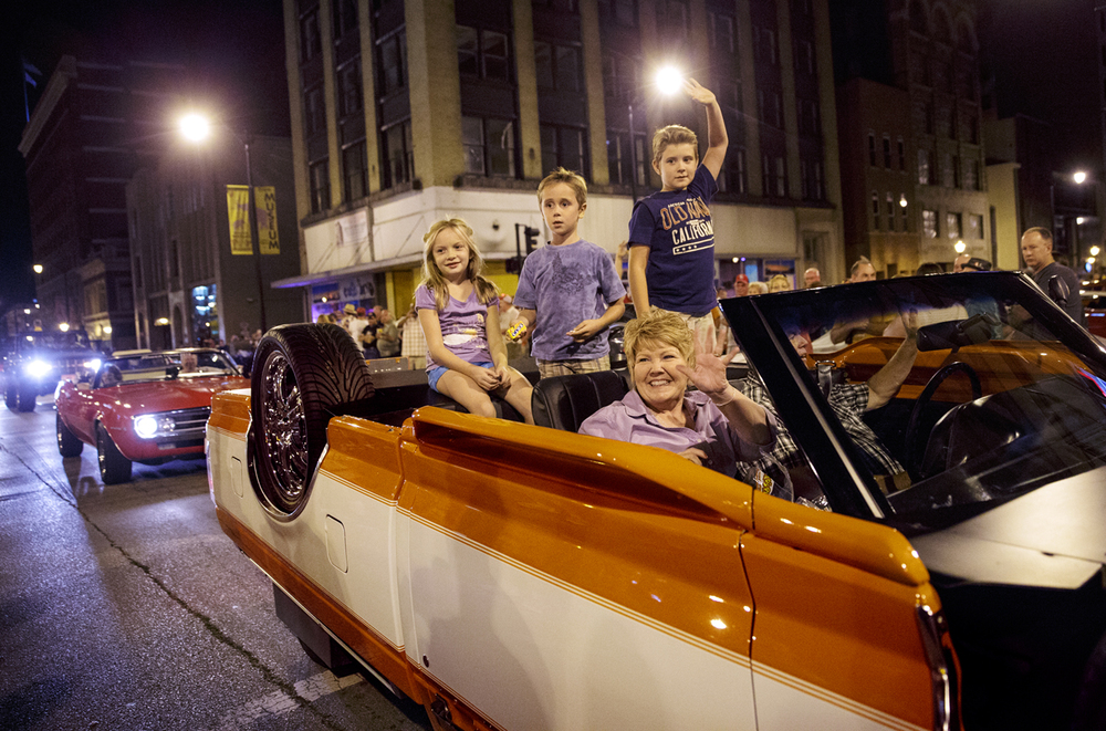 Kathy Sullivan, left, waves to the crowd as her husband Rick drives their niece Hailey Hayes, and nephews Brock and Brody Wilson, through the crowd on Sixth Street during the Route 66 Mother Road Festival Friday night cruise. The upside down truck was inspired by a customer of Sullivan's business, Kathy's Collision Center, in Clinton, Ill., who flipped her truck into a snow bank. The Sullivan's truck took five months and parts from two different trucks to complete.  Ted Schurter/The State Journal-Register