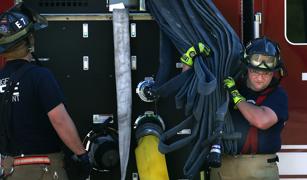 "Station 7 firefighter Kurt Leonard pulls auxiliary fire hose off of Truck 2 Quint (based at Station 2) in preparation for testing on Wednesday, Oct. 22, 2014. This particular Quint has nearly 2000 feet of hose onboard ranging from 1 3/4"" to 5."" Annual pressure testing for every fire hose on Springfield Fire Department trucks from all 12 stations is taking place this week and next at Happy Hollow at the Illinois State Fairgrounds in Springfield. All hoses are extended fully from each truck and charged for five minutes at 250 psi to determine if there are leaks or other issues. David Spencer/The State Journal-Register"