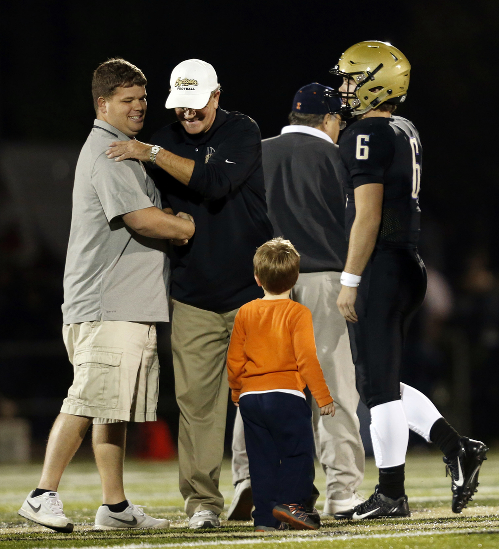 Rochester head coach Derek Leonard greets his dad and Sacred Heart-Griffin head coach Ken Leonard on the field before kick off Friday, Oct. 24, 2014. Ted Schurter/The State Journal-Register