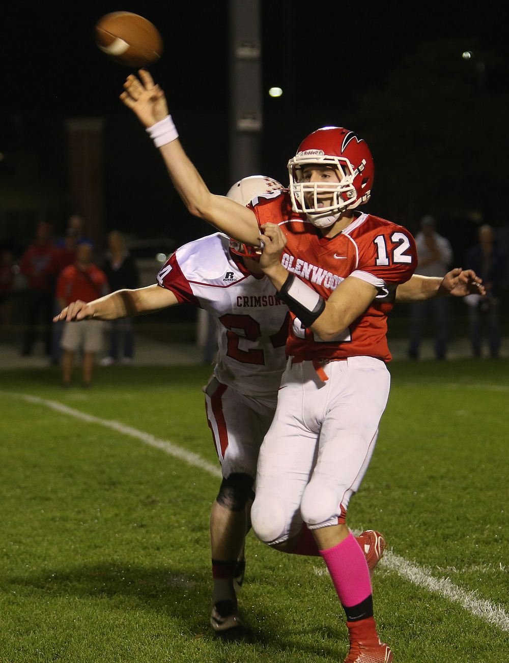 Titans quarterback Zach Leighton gets the ball off before being tackled by Crimsons defender Dillon Pennell. The Chatham Glenwood High School Titans defeated the Jacksonville High School Crimsons 49-35 in football action on Friday evening, Oct. 24, 2014. David Spencer/The State Journal-Register
