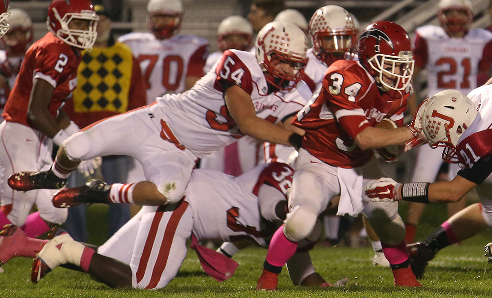 Crimsons defender Zach Stout goes airborne while trying to stop Titans ball carrier Josh Talley. The Chatham Glenwood High School Titans defeated the Jacksonville High School Crimsons 49-35 in football action on Friday evening, Oct. 24, 2014. David Spencer/The State Journal-Register