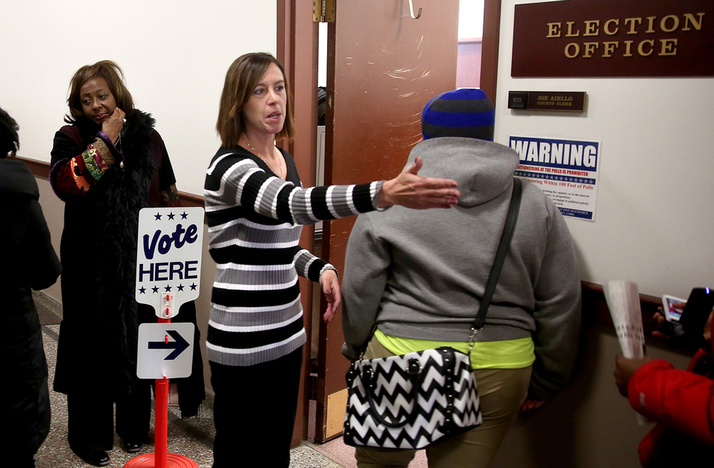 "Sangamon County Clerk's office employee Stacey Kern directs people in line to vote on Saturday morning. Known as ""Souls to the Polls"", an effort to get the word out to vote early this Sunday in advance of Tuesday's election and to protect voting rights and celebrate the 50th anniversary of the Civil Rights Act, a rally was held at the Boys and Girls Club of Central Illinois in Springfield on Saturday, Nov. 1, 2014. A march of rally participants followed to the Sangamon County Election Office in the County building where people had the opportunity to vote early Saturday morning.   David Spencer/The State Journal-Register"