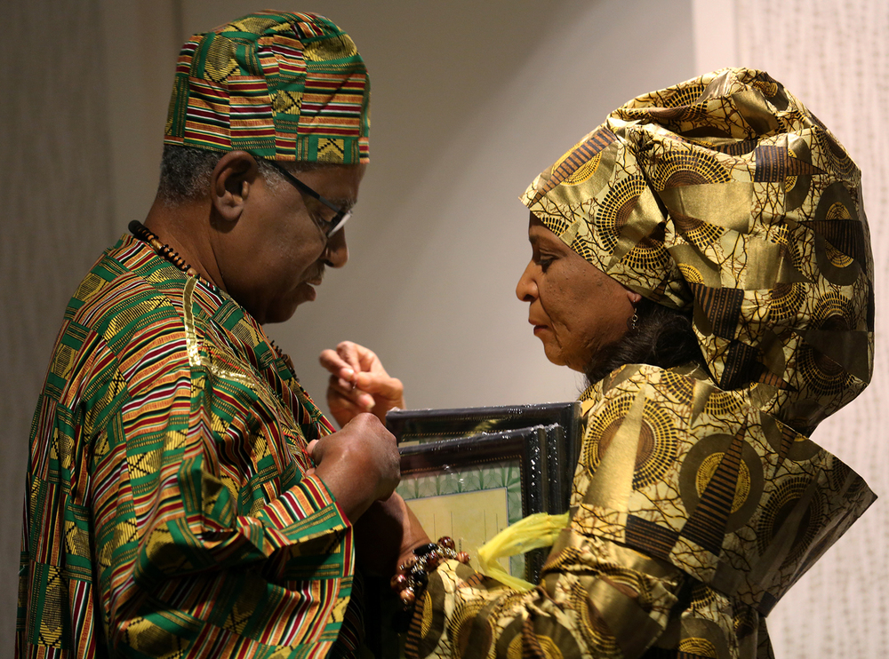 "Many of those attending the gala Thursday evening wore traditional African dress, including event co-chair Ernestine Lawrence of Springfield, who helps her husband Archie Lawrence with a last-minute adjustment to his outfit before the start of the dinner. ""Honoring our Heritage & Celebrating the Motherland, Africa"" were the themes of the third annual gala for the Springfield & Central Illinois African American History Museum which took place at the Springfield Hilton on Thursday evening, Oct. 30, 2014. A fundraiser for the museum's exhibition and education  programming, the event featured a dinner and included performances by the African Ensemble of Central Illinois, Soul Fresh, a progressive jazz and blues band, vendors, an art show and silent auction. David Spencer/The State Journal-Register"