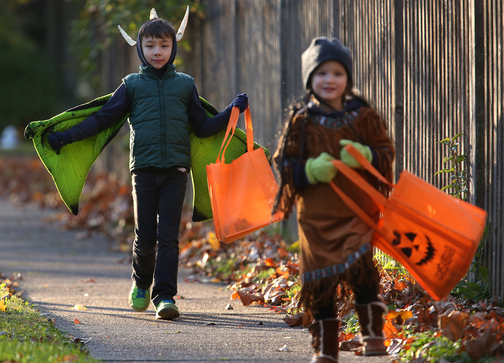 Blending winter jackets and caps with Halloween costumes was a necessity because of frigid conditions Friday night. Liam Moore, 7, of Springfield spreads his dragon wings while his hat is adorned with horns fashioned from recycled aluminum carry-out containers. Friend and fellow trick or treater Mack Metzger, 7, wears her Pocahontas costume while both head to Noble Ave. to gather more treats. Springfield area children officially celebrated Halloween with trick or treating across the city on Friday evening, Oct. 31, 2014. David Spencer/The State Journal-Register