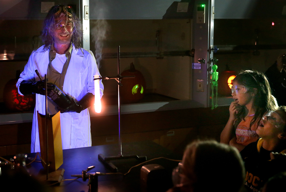 "Chemistry club president Leonard Smith, doing an admirable job as a mad scientist, demonstrated how breaking oxygen bonds in a Gummy Bear using a reagent of potassium chlorate placed in a test tube and subjected to heat will release energy, much to the delight of children looking on at right Tuesday night. The Lincoln Land Community College Chemistry and Environmental clubs hosted their second annual ""Haunted Lab"" on Tuesday evening, Oct. 28, 2014. Children, many dressed in Halloween costumes, got to see LLCC students from the two clubs conduct chemical expirements at six different stations, with the main purpose according to professor of chemistry Jennifer Ramm for the children to get excited about science and to see how science has real life applications. David Spencer/The State Journal-Register"