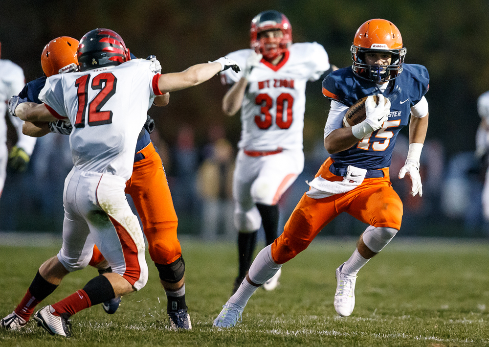 Rochester's Jeremy Bivens (15) cuts away on a block from his teammate against Mt. Zion's Austin Thacker (12) in the first half during the first round of the Class 4A playoffs at Rocket Booster Field, Saturday, Nov. 1, 2014, in Rochester, Ill. Justin L. Fowler/The State Journal-Register