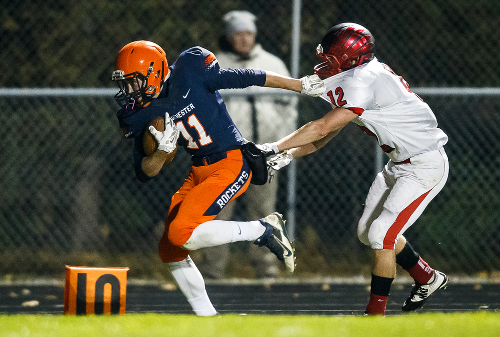 Rochester's Collin Etherton (11) breaks free from Mt. Zion's Austin Thacker (12) on his way to a 40-yard touchdown reception in the first half during the first round of the Class 4A playoffs at Rocket Booster Field, Saturday, Nov. 1, 2014, in Rochester, Ill. Justin L. Fowler/The State Journal-Register